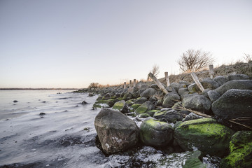 Rocks covered with green moss by a frozen lake