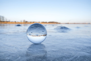 Transparent glass orb on a frozen lake with ice