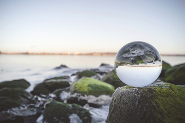 Glass orb on rocks by the sea