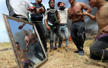 Palestinian protesters are seen reflected in a mirror during clashes with Israeli troops at the Israel-Gaza border, in the southern Gaza Strip