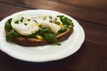 Tasty poached egg on toast over rustic background