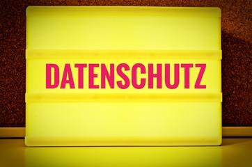 Leuchtpanel  mit der Aufschrift in deutsch Datenschutz vor einer Pinnwand, auf englisch Privacy Policy, in gelb mit rosa Schrift