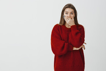Studio portrait of shocked amazed attractive woman in loose sweater, covering opened mouth with palm and staring terrified at camera, being astonished and surprised over gray background