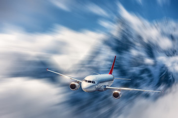 Obraz Modern airplane mith motion blur effect at sunny bright day. Landscape with passenger airplane, blurred clouds, mountains, blue sky. Passenger aircraft in motion. Business travel. Commercial plane - fototapety do salonu