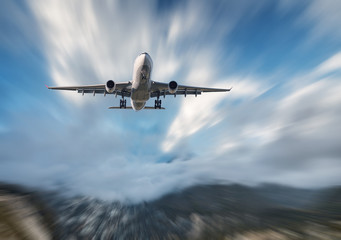 Obraz Big airplane mith motion blur effect at sunny bright day. Landscape with passenger airplane, blurred clouds, mountains, blue sky. Passenger aircraft in motion. Business travel. Commercial aircraft - fototapety do salonu