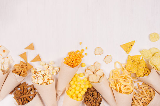 Beige paper cones with bright crunchy fast food snacks - nachos, popcorn, croutons, chips on white wood board, copy space.