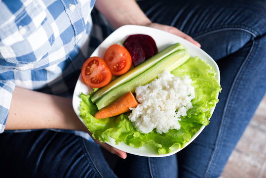 Girl with a plate of vegetables in hands. Healthy eating concept. A girl in jeans and a plaid shirt. Casual Style. Proper nutrition. Diet. Health. Vegetarian food. Vegans food. Small depth of field.