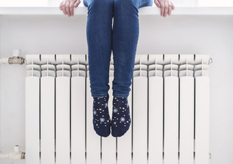 The girl sits on the windowsill and warms her feet in pretty socks at the radiator, on a cold winter day.