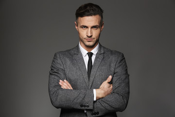 Image of mature unshaved man wearing business suit looking on camera with strict determined gaze, isolated over gray background