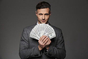 Photo of confident guy 30s in business suit holding fan of money dollar bills and looking on camera, isolated over gray background
