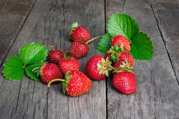 Ripe strawberry with green leaves on wooden table. Closeup photo.
