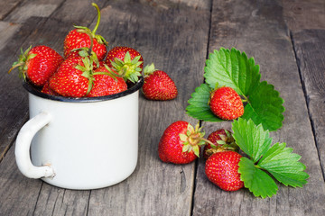Ripe strawberry in metal mug on wooden table. 
