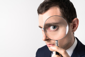 Young man holding a magnifying glass.