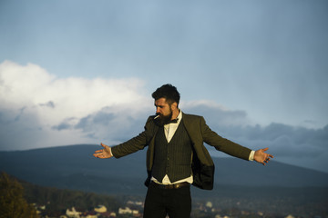 Hipster with stylish appearance in front of dramatic sky, skyline.
