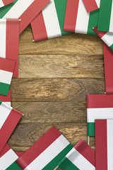 Hungary small flags framing a wood texture background with copy space