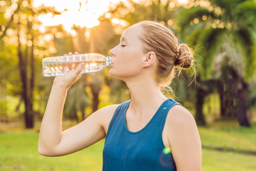 Attractive sporty woman drinking water from a bottle after jogging or running