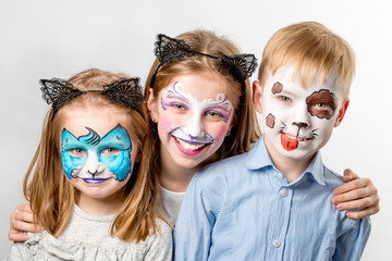Children with animal face paintings isolated