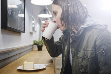 Thoughtful woman drinking cappuccino in a paper cup and eating a cheesecake in a cozy cafe. Close-up.