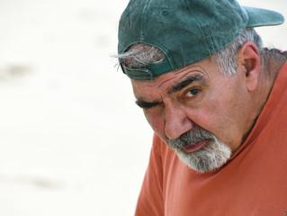 elderly Lebanese man with gray mustache and goatee wearing baseball cap backwards