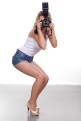 Young sexy woman is a professional photographer with slr camera