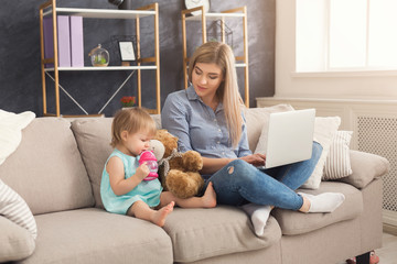 Young mother working and spending time with baby