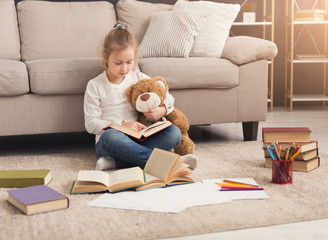 Happy little female child hugging her teddy bear and reading