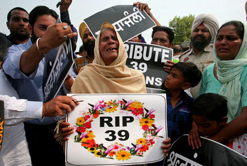 A relative of one of the 38 Indian construction workers who were killed by Islamic State militants in Iraq in 2014, mourns as she waits for mortal remains of the deceased to arrive outside the airport in Amritsar