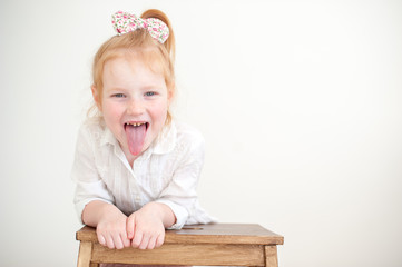 Girl showing tongue on the white background