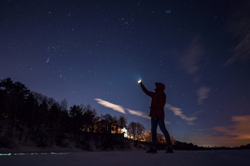 A man looks at stars frosty winter at night and shines in the sky