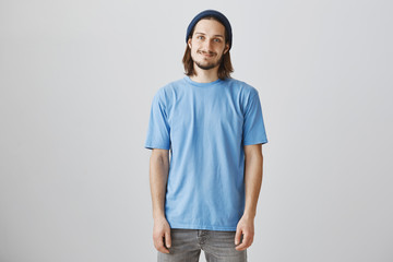 Handsome urban guy likes skating and hanging out. Indoor shot of attractive hipster man in blue beanie and t-shirt, smiling shy and standing casually over gray background, expressing friendliness