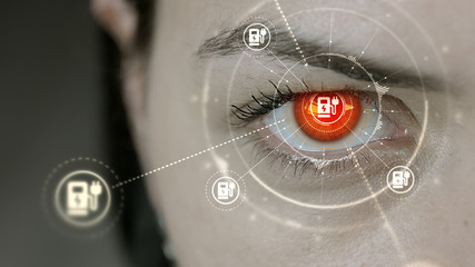 Young cyborg female blinks then car charging station symbols appears.