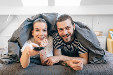 Young couple laying in the bed and watching tv