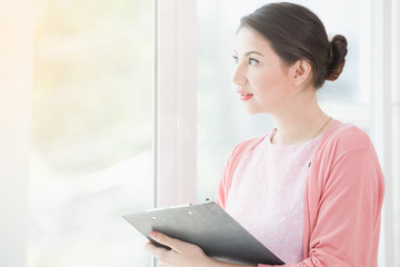 Business woman standing working near a window and holding clipboard at office.