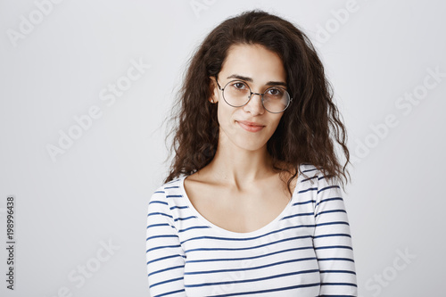 Waist Up Shot Of Cute Smart Curly Haired Girl In Round Glasses