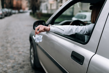 Female hand throwing trash out of car window.