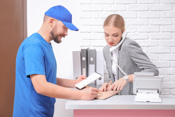 Female receptionist receiving parcel at workplace