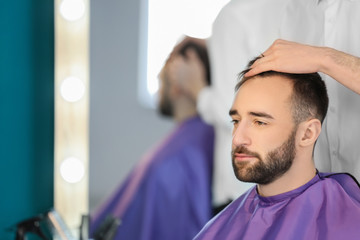 Professional hairdresser working with client in salon