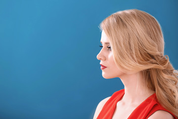 Young woman with beautiful curls on color background. Professional hairdresser's work
