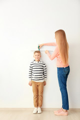 Young woman measuring height of little boy near light wall