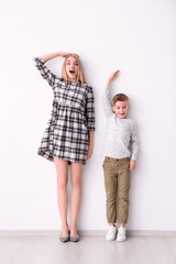 Young woman and little boy measuring height near light wall