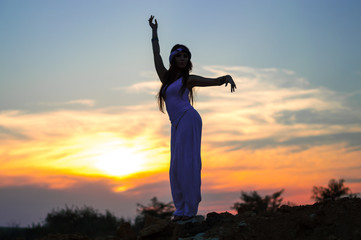 Dark-haired girl in white clothes dancing Oriental dance. Silhouette. Nature. Sunset. Mountainous...