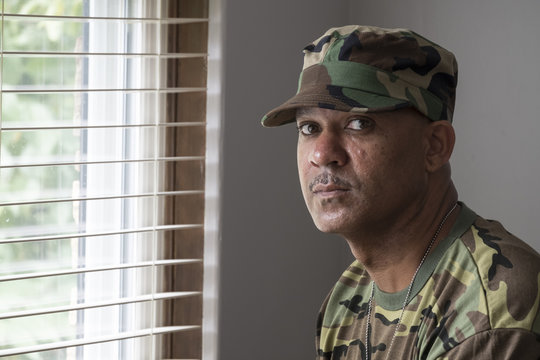 Portrait of a black man in military fatigues, looking at the camera