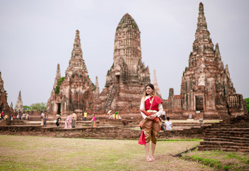Thai girl wearing traditional thai costumes at Wat Chaiwatthanaram is a Buddhist temple in the city of Ayutthaya Historical Park, Thailand.
