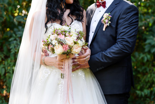 Beautiful lush bridal bouquet with lace ribbons in bride's hand. Happy bride and groom hugging after wedding ceremony, free space. Wedding couple, newlyweds, free space