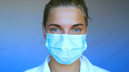 Young beautiful woman, nurse, doctor, in mask, white blue background.