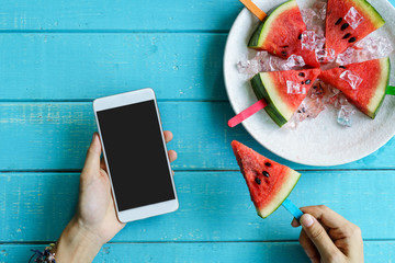 Watermelon slice popsicles with colorful stick and hand holding smart phone on wooden background, Summer fruits
