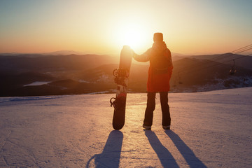 Portrait of snowboarder staying back to camera, watching sunrise on mountain top
