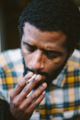 Portrait of guy smoking cigarette. Mixed race man with african hair, dark skin and black beard