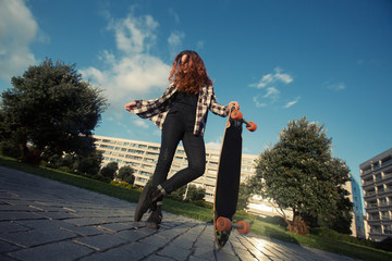 Young happy female have fun and riding on skate longboard outdoor