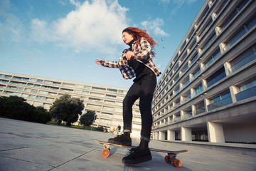 Young happy female study how to riding on skate longboard outdoor